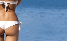 Sexy woman buttocks on tropical beach background near ocean. Close up outdoor shot of young woman in white bikini, sunbathing at sea shore.